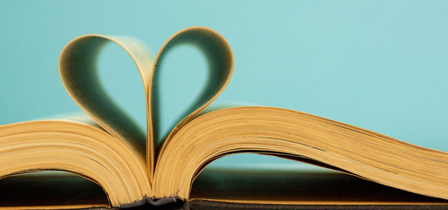 The pages of the book are curved in the shape of a heart. Opened book on a blue background. Back to school theme concept. Bibliophile.